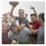 Hombre que aumenta el balón de fútbol que celebra  azulejos cerámicos
