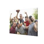 Hombre que aumenta el balón de fútbol que celebra  impresiones en lona estiradas