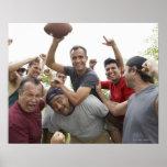 Hombre que aumenta el balón de fútbol que celebra  poster
