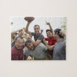 Hombre que aumenta el balón de fútbol que celebra  puzzle con fotos