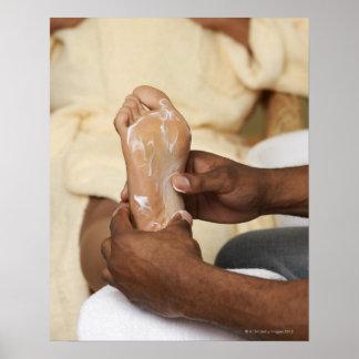 Hombre que da masajes al pie de la mujer póster