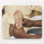 Hombre que da masajes al pie de la mujer tapetes de ratón