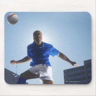 Hombre que despide el balón de fútbol en su cabeza mouse pads