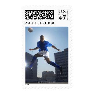 Hombre que despide el balón de fútbol en su cabeza timbres postales