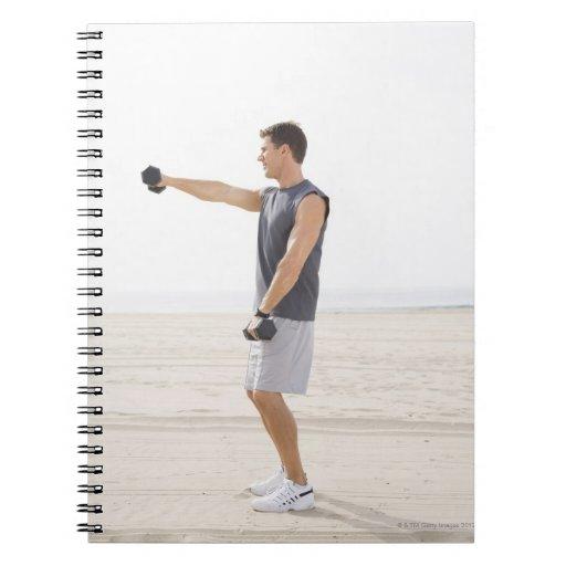 Hombre que ejercita en la playa spiral notebooks