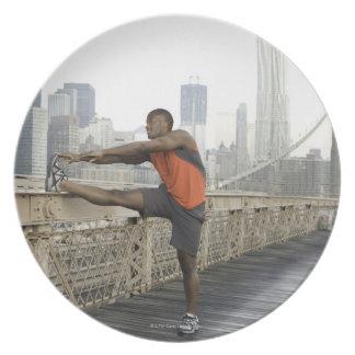 Hombre que estira en el puente de Brooklyn Platos Para Fiestas
