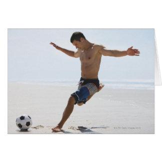 Hombre que golpea el balón de fútbol con el pie en felicitaciones