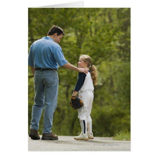 Hombre que habla con el chica en uniforme del béis tarjeta