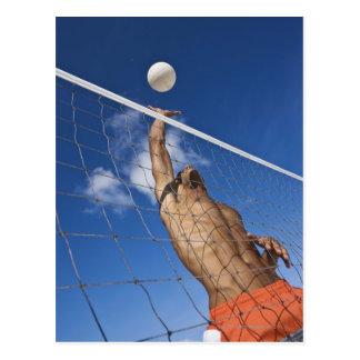Hombre que juega a voleibol de playa postal