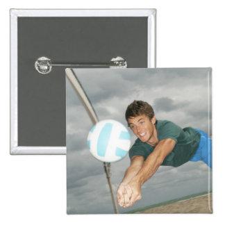 Hombre que juega a voleibol en la playa pin cuadrada 5 cm