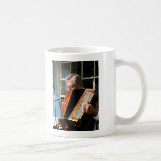 Hombre que juega el acordeón taza de café