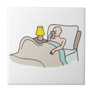 Hombre que lee su teléfono en cama azulejo cuadrado pequeño