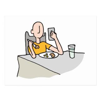 Hombre que lee su teléfono mientras que come postal