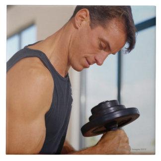 Hombre que levanta una pesa de gimnasia azulejo cuadrado grande