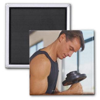 Hombre que levanta una pesa de gimnasia iman para frigorífico