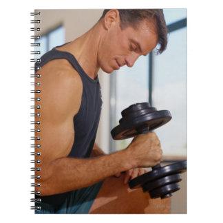 Hombre que levanta una pesa de gimnasia cuadernos