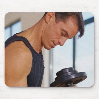 Hombre que levanta una pesa de gimnasia tapetes de ratones