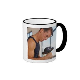 Hombre que levanta una pesa de gimnasia taza de café
