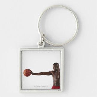 Hombre que lleva a cabo baloncesto llavero cuadrado plateado