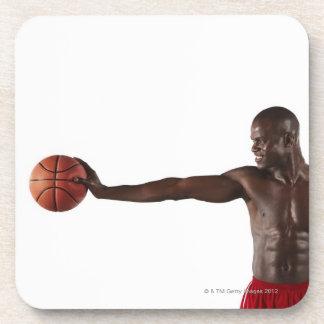 Hombre que lleva a cabo baloncesto posavasos de bebidas