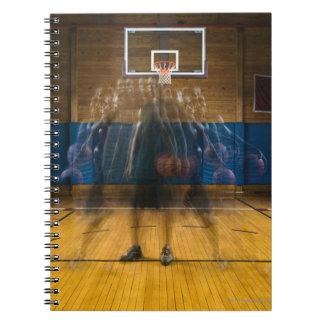 Hombre que lleva a cabo el baloncesto que se libretas