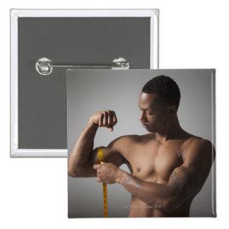 Hombre que mide su tríceps pins