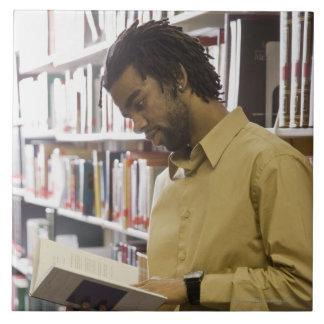 Hombre que mira el libro en biblioteca azulejo cuadrado grande