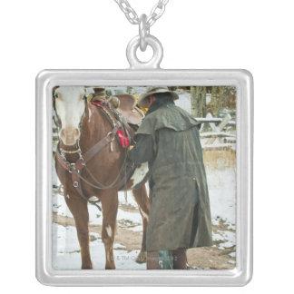 Hombre que pone la silla de montar en caballo collar plateado