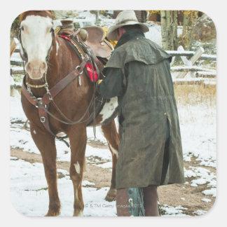 Hombre que pone la silla de montar en caballo pegatina cuadrada