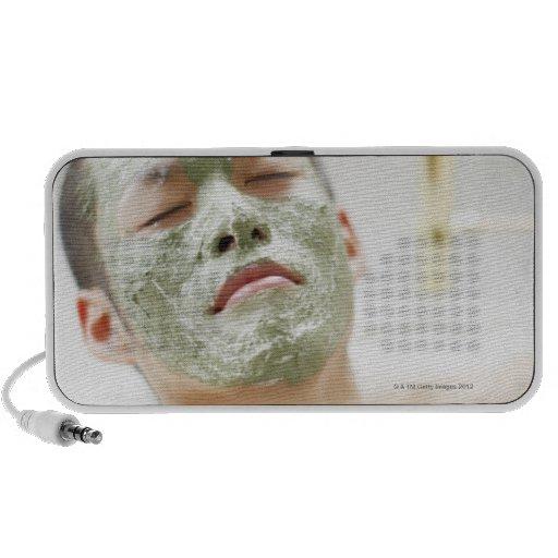 Hombre que se relaja en una bañera con una máscara mini altavoces