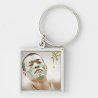 Hombre que se relaja en una bañera con una máscara llavero cuadrado plateado
