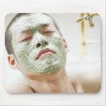 Hombre que se relaja en una bañera con una máscara alfombrilla de raton