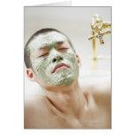 Hombre que se relaja en una bañera con una máscara tarjeta