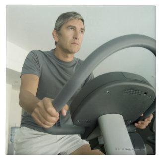 Hombre que se resuelve en un gimnasio azulejo cuadrado grande