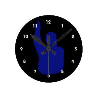 hombre que señala encima de azul de la sombra relojes de pared