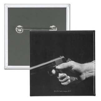 Hombre que sostiene el arma pin cuadrado