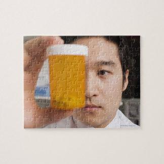 Hombre que sostiene la botella de píldora puzzle con fotos