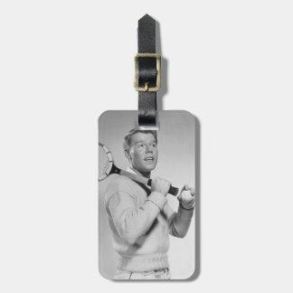 Hombre que sostiene la estafa de tenis etiqueta para maleta