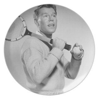 Hombre que sostiene la estafa de tenis platos de comidas