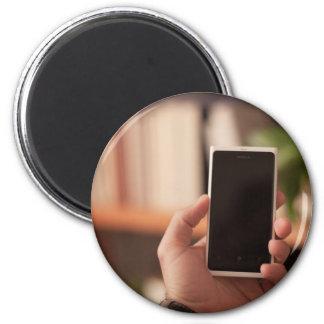 Hombre que sostiene su smartphone en su mano imán redondo 5 cm