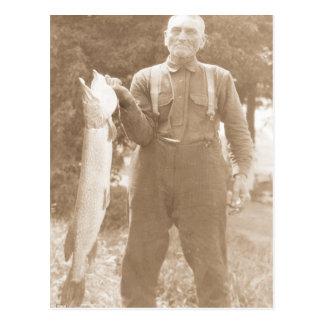 Hombre que sostiene un pescado postales