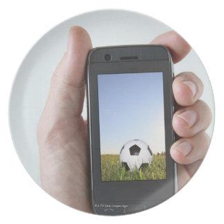 Hombre que sostiene un teléfono móvil plato