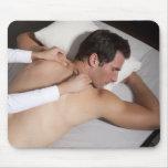 Hombre que tiene un masaje trasero de la mujer mousepads