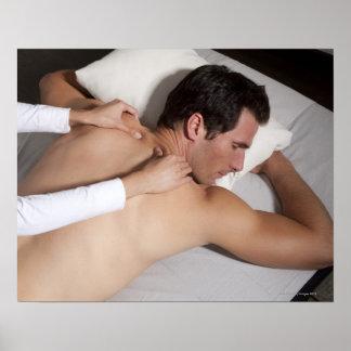 Hombre que tiene un masaje trasero de la mujer póster