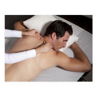 Hombre que tiene un masaje trasero de la mujer tarjeta postal
