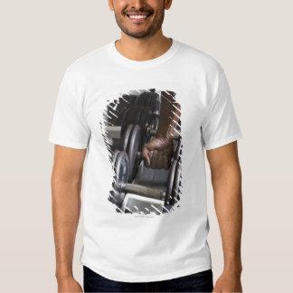 Hombre que toma el peso del estante camisas
