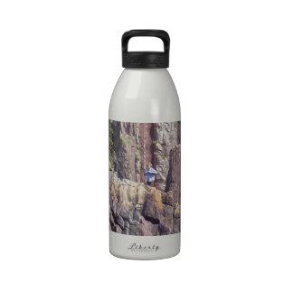 Hombre salvaje en los acantilados botellas de agua reutilizables