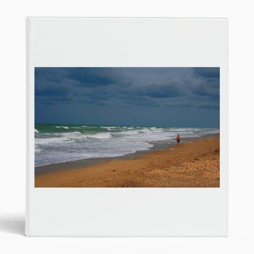 Hombre solitario que camina en la playa tempestuos