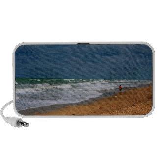 Hombre solitario que camina en la playa tempestuos altavoz de viajar
