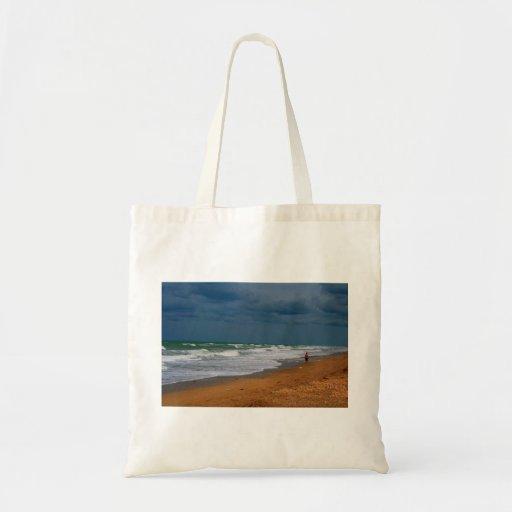 Hombre solitario que camina en la playa tempestuos bolsas